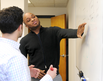 Adelphi psychology students work at whiteboard