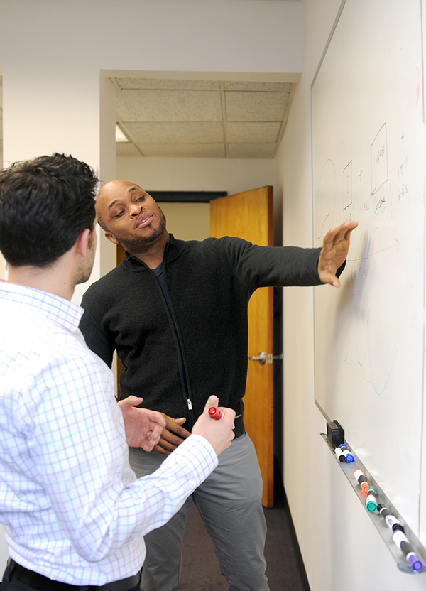 Adelphi psychology students work at whiteboard.
