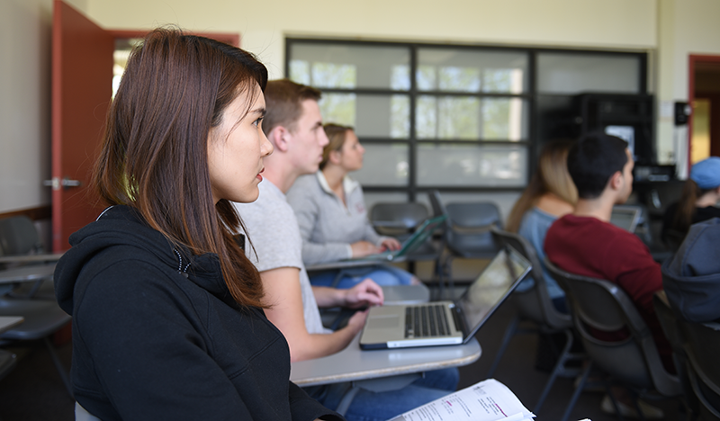 Adelphi business student listens in class with laptop.