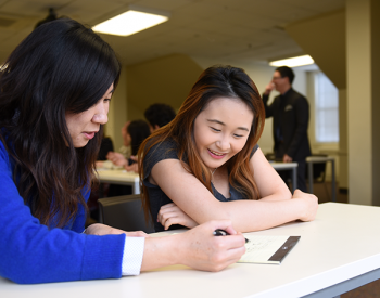 Two female students study together at a table