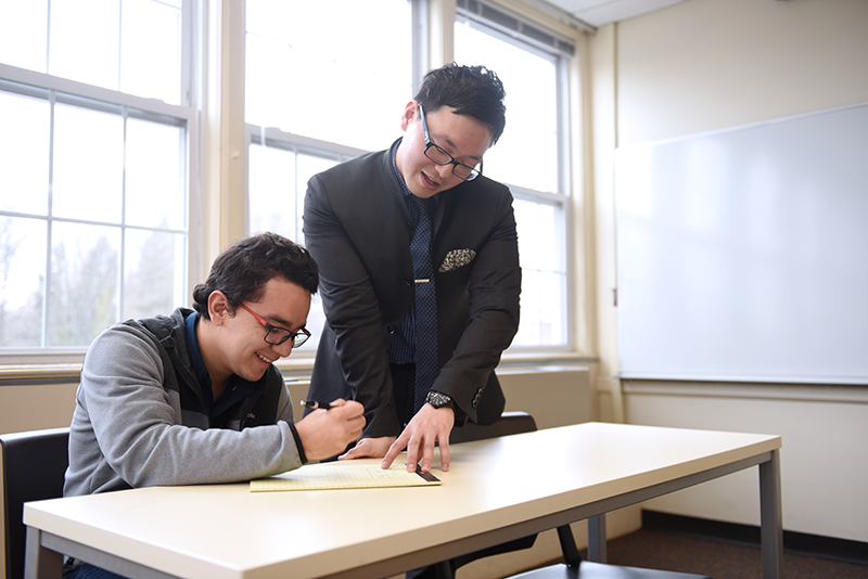Two male students working together at a table