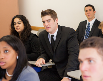 Adelphi business students in suits seated in a classroom.